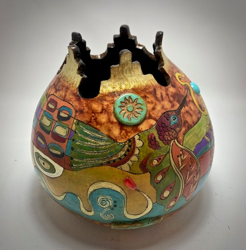 A decorative gourd container with lots of color and a bird