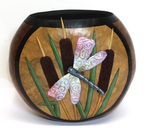 A decorative gourd container with a draonfly and some cattails