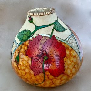 A decorative gourd container with flowers