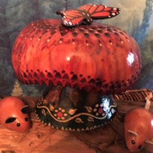 A decorative gourd in the shape of a mushroom with some decorative mice