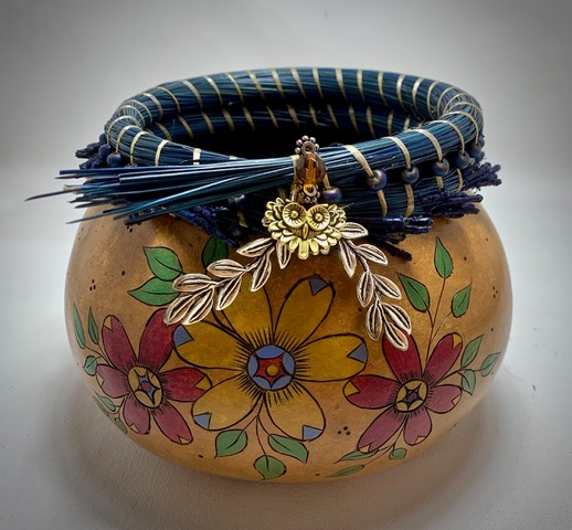 A decorative gourd flower bowl with flowers painted on it